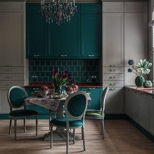 Idee per una grande cucina classica con lavello integrato, top in superficie solida, paraspruzzi verde, paraspruzzi con piastrelle in ceramica, elettrodomestici in acciaio inossidabile, nessuna isola, pavimento marrone, ante con riquadro incassato e ante grigie