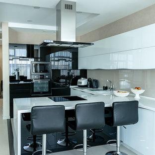 Идея дизайна: угловая кухня-гостиная среднего размера в современном стиле с накладной раковиной, плоскими фасадами, черными фасадами, столешницей из акрилового камня, бежевым фартуком, фартуком из керамогранитной плитки, черной техникой, полом из керамогранита, полуостровом, бежевым полом и белой столешницей