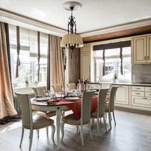 Пример оригинального дизайна интерьера: кухня в стиле кантри с искусственно-состаренными фасадами, серым фартуком и белой техникой