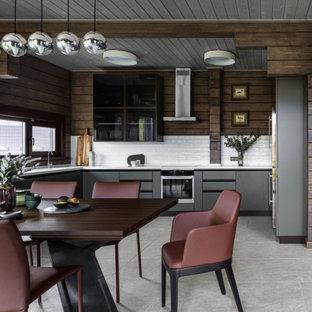 Идея дизайна: большая п-образная кухня в современном стиле с обеденным столом, плоскими фасадами, серыми фасадами, белым фартуком, техникой из нержавеющей стали, серым полом и белой столешницей без острова