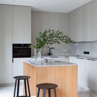 Стильный дизайн: угловая кухня среднего размера в стиле модернизм с врезной раковиной, плоскими фасадами, серыми фасадами, островом, белым полом и серой столешницей - последний тренд