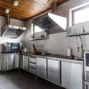 Стильный дизайн: угловая кухня в стиле лофт с монолитной раковиной, плоскими фасадами, кухней из нержавеющей стали, столешницей из нержавеющей стали, белым фартуком, серым полом и техникой из нержавеющей стали без острова - последний тренд
