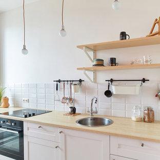 Неиссякаемый источник вдохновения для домашнего уюта: маленькая отдельная, линейная кухня в скандинавском стиле с накладной раковиной, белыми фасадами, белым фартуком, фартуком из плитки кабанчик, черной техникой и фасадами с выступающей филенкой без острова