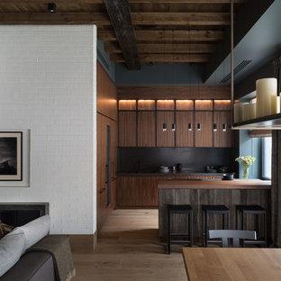 Пример оригинального дизайна: угловая кухня-гостиная среднего размера в стиле лофт с фасадами цвета дерева среднего тона, столешницей из кварцита, плоскими фасадами, черным фартуком, светлым паркетным полом, бежевым полом, черной столешницей и полуостровом