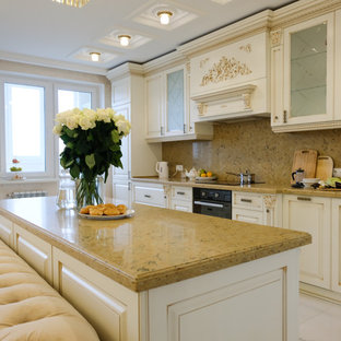 Inspiration for a large traditional galley open plan kitchen in Moscow with raised-panel cabinets, beige cabinets, quartz benchtops, brown splashback, marble splashback, black appliances, marble floors, with island, beige floor and brown benchtop.
