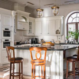 На фото: угловая кухня в классическом стиле с раковиной в стиле кантри, фасадами с выступающей филенкой, белыми фасадами, белой техникой, островом и белым фартуком с