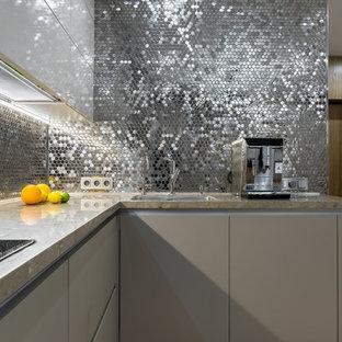 На фото: угловая кухня-гостиная в современном стиле с врезной раковиной, плоскими фасадами, серыми фасадами, фартуком цвета металлик, фартуком из плитки мозаики и бежевой столешницей
