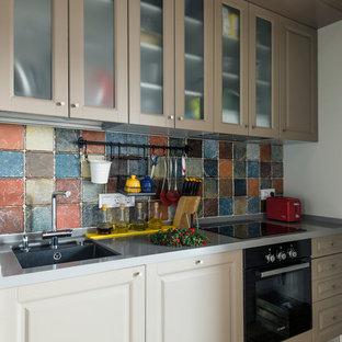 Свежая идея для дизайна: линейная кухня в современном стиле с обеденным столом, врезной раковиной, фасадами с выступающей филенкой, серыми фасадами, разноцветным фартуком и черной техникой - отличное фото интерьера