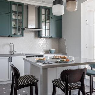 На фото: маленькая отдельная, угловая кухня в стиле современная классика с врезной раковиной, зелеными фасадами, столешницей из акрилового камня, серым фартуком, фартуком из керамической плитки, полом из керамической плитки, островом, серым полом, серой столешницей и фасадами с утопленной филенкой с
