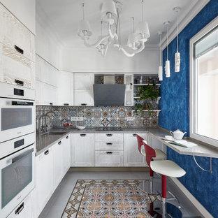 Новые идеи обустройства дома: п-образная кухня в современном стиле с врезной раковиной, фасадами в стиле шейкер, белыми фасадами, разноцветным фартуком, фартуком из плитки мозаики, полуостровом, серым полом и серой столешницей