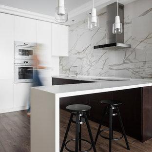 Foto på ett funkis vit u-kök, med släta luckor, bruna skåp, vitt stänkskydd, vita vitvaror, en halv köksö och brunt golv