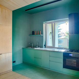 Новый формат декора квартиры: линейная кухня в современном стиле с накладной раковиной, плоскими фасадами, бирюзовыми фасадами, черной техникой, бирюзовым полом и серой столешницей без острова