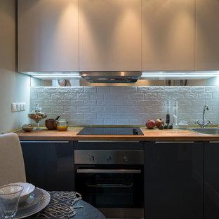 モスクワの小さいエクレクティックスタイルのおしゃれなキッチン (ドロップインシンク、フラットパネル扉のキャビネット、白いキャビネット、木材カウンター、白いキッチンパネル、セラミックタイルのキッチンパネル、シルバーの調理設備の、スレートの床、アイランドなし) の写真