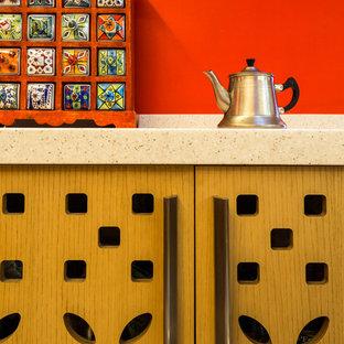 他の地域の中サイズの地中海スタイルのおしゃれなキッチン (フラットパネル扉のキャビネット、オレンジのキャビネット、赤いキッチンパネル、シルバーの調理設備の、ベージュの床) の写真