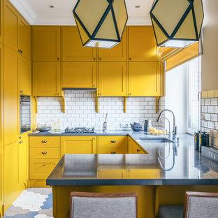 Diseño de cocina en U, contemporánea, abierta, con fregadero bajoencimera, armarios con paneles empotrados, puertas de armario amarillas, salpicadero blanco, electrodomésticos negros y península