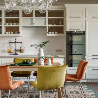 Стильный дизайн: линейная кухня среднего размера в стиле современная классика с обеденным столом, фасадами с утопленной филенкой, белыми фасадами, белым фартуком, фартуком из цементной плитки, техникой под мебельный фасад, разноцветным полом и белой столешницей без острова - последний тренд