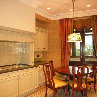 モスクワの広いヴィクトリアン調のおしゃれなL型キッチン (レイズドパネル扉のキャビネット、ベージュのキャビネット、クオーツストーンカウンター、ベージュキッチンパネル、セラミックタイルのキッチンパネル、セラミックタイルの床、アイランドなし、緑のキッチンカウンター、マルチカラーの床) の写真