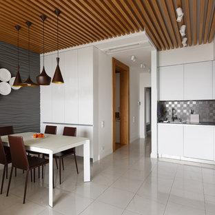 Выдающиеся фото от архитекторов и дизайнеров интерьера: угловая кухня среднего размера в современном стиле с обеденным столом, плоскими фасадами, белыми фасадами, серым фартуком, техникой из нержавеющей стали и белым полом без острова