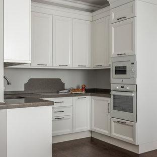 Стильный дизайн: маленькая п-образная кухня в стиле современная классика с врезной раковиной, фасадами с утопленной филенкой, белыми фасадами, серым фартуком, белой техникой, темным паркетным полом, коричневым полом и серой столешницей без острова - последний тренд