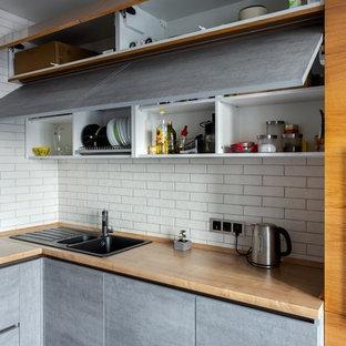 Ejemplo de cocina en L, contemporánea, pequeña, cerrada, sin isla, con encimera de laminado, salpicadero blanco, salpicadero de ladrillos, electrodomésticos negros y suelo de baldosas de cerámica