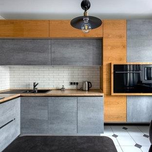 Идея дизайна: угловая кухня в современном стиле с столешницей из ламината, белым фартуком, фартуком из кирпича, черной техникой, полом из керамической плитки, двойной раковиной, плоскими фасадами, серыми фасадами и разноцветным полом без острова