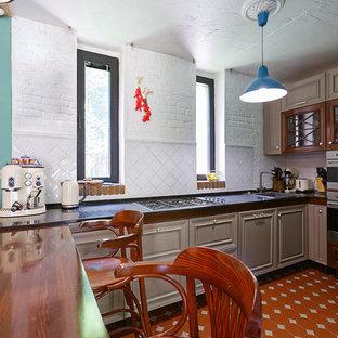 モスクワの中くらいのトランジショナルスタイルのおしゃれなキッチン (ドロップインシンク、レイズドパネル扉のキャビネット、濃色木目調キャビネット、クオーツストーンカウンター、白いキッチンパネル、レンガのキッチンパネル、シルバーの調理設備、セラミックタイルの床、アイランドなし、オレンジの床、黒いキッチンカウンター) の写真