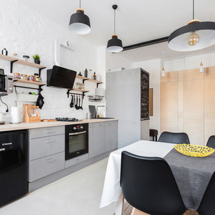 Пример оригинального дизайна: прямая кухня среднего размера в стиле лофт с обеденным столом, накладной раковиной, серыми фасадами, деревянной столешницей, белым фартуком, черной техникой, полом из фанеры, бежевым полом и плоскими фасадами без острова