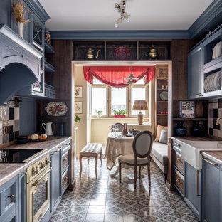 モスクワのトラディショナルスタイルのおしゃれなキッチン (エプロンフロントシンク、シェーカースタイル扉のキャビネット、青いキャビネット、マルチカラーのキッチンパネル、セラミックタイルのキッチンパネル、カラー調理設備、アイランドなし、マルチカラーの床、茶色いキッチンカウンター) の写真