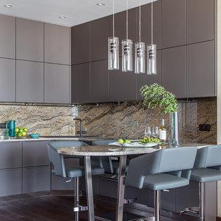 На фото: п-образная кухня в современном стиле с плоскими фасадами, серыми фасадами, коричневым фартуком, фартуком из каменной плиты, темным паркетным полом, полуостровом, коричневым полом и коричневой столешницей