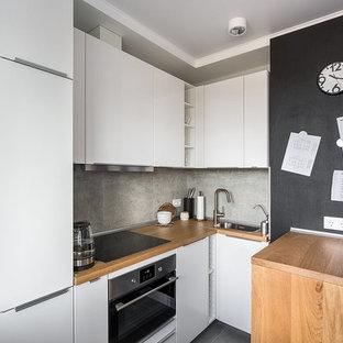 Пример оригинального дизайна: угловая кухня в скандинавском стиле с накладной раковиной, плоскими фасадами, белыми фасадами, столешницей из дерева, серым фартуком, техникой из нержавеющей стали, полуостровом, серым полом и коричневой столешницей