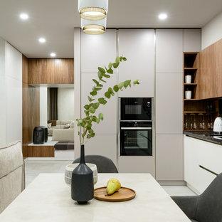 Создайте стильный интерьер: угловая кухня-гостиная в современном стиле с врезной раковиной, плоскими фасадами, белыми фасадами, черным фартуком, черной техникой, белым полом и черной столешницей - последний тренд