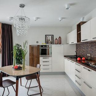 Создайте стильный интерьер: угловая кухня в современном стиле с накладной раковиной, плоскими фасадами, белыми фасадами, коричневым фартуком, серым полом, фартуком из удлиненной плитки и техникой из нержавеющей стали без острова - последний тренд