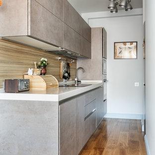 Cette image montre une cuisine linéaire design fermée avec un placard à porte plane, des portes de placard grises, une crédence beige, un sol en bois brun, aucun îlot, un sol marron et un plan de travail blanc.