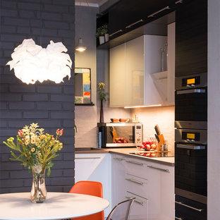 Выдающиеся фото от архитекторов и дизайнеров интерьера: угловая кухня-гостиная в современном стиле с накладной раковиной, плоскими фасадами, белыми фасадами и техникой из нержавеющей стали без острова