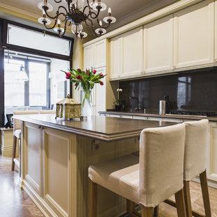 Новый формат декора квартиры: отдельная, линейная кухня в классическом стиле с фасадами с утопленной филенкой, белыми фасадами, черным фартуком и островом