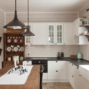 На фото: угловые кухни в скандинавском стиле с раковиной в стиле кантри, фасадами в стиле шейкер, белыми фасадами, белым фартуком, черной техникой, островом и коричневым полом