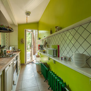 Design ideas for an eclectic single-wall separate kitchen in Saint Petersburg with a drop-in sink, raised-panel cabinets, light wood cabinets, wood benchtops, stainless steel appliances and no island.