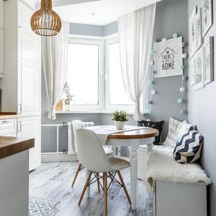 Свежая идея для дизайна: угловая кухня в скандинавском стиле с обеденным столом, светлым паркетным полом, серым полом, фасадами с выступающей филенкой, белыми фасадами и коричневой столешницей без острова - отличное фото интерьера