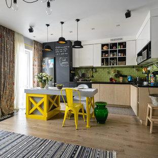 Новые идеи обустройства дома: кухня в современном стиле с плоскими фасадами, белыми фасадами, зеленым фартуком, фартуком из плитки кабанчик, черной техникой, островом и коричневым полом