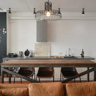 На фото: угловые кухни-гостиные в стиле лофт с накладной раковиной, плоскими фасадами, бежевыми фасадами, белым фартуком, черной техникой, паркетным полом среднего тона и островом