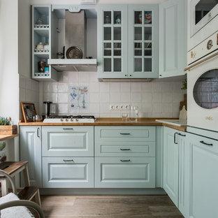 Неиссякаемый источник вдохновения для домашнего уюта: угловая кухня в современном стиле с накладной раковиной, фасадами с выступающей филенкой, столешницей из дерева, белым фартуком и белой техникой