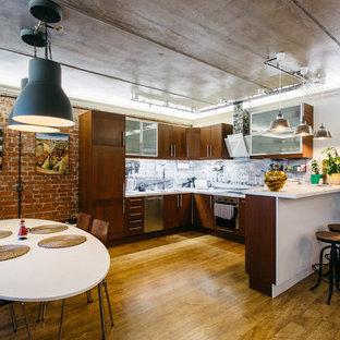 Новый формат декора квартиры: п-образная кухня-гостиная в стиле лофт с фасадами цвета дерева среднего тона, серым фартуком, техникой из нержавеющей стали, паркетным полом среднего тона и полуостровом