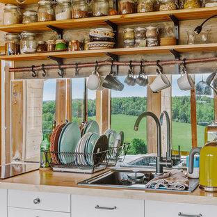 На фото: кухня в современном стиле с плоскими фасадами, белыми фасадами, столешницей из дерева и фартуком с окном с