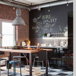 Неиссякаемый источник вдохновения для домашнего уюта: линейная кухня-гостиная в стиле лофт с плоскими фасадами, черными фасадами, черным фартуком, черной техникой и островом