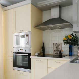 Пример оригинального дизайна: маленькая отдельная, угловая кухня в классическом стиле с накладной раковиной, фасадами в стиле шейкер, желтыми фасадами, белым фартуком, техникой из нержавеющей стали и бежевым полом без острова