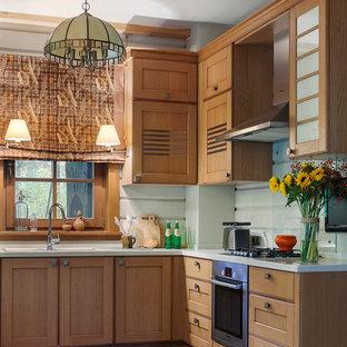 Новый формат декора квартиры: угловая кухня в стиле кантри с двойной раковиной, фасадами в стиле шейкер, фасадами цвета дерева среднего тона, белым фартуком, фартуком из стекла и техникой из нержавеющей стали