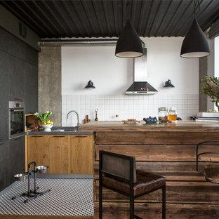 Свежая идея для дизайна: угловая кухня-гостиная в стиле лофт с накладной раковиной, плоскими фасадами, фасадами цвета дерева среднего тона, белым фартуком, техникой из нержавеющей стали и островом - отличное фото интерьера