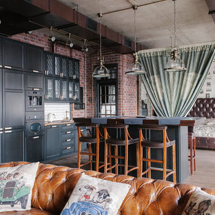 Новые идеи обустройства дома: линейная кухня-гостиная в стиле лофт с фасадами в стиле шейкер, черными фасадами, белым фартуком, черной техникой, паркетным полом среднего тона, островом и коричневым полом