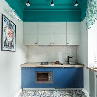 На фото: отдельная, линейная кухня в стиле фьюжн с накладной раковиной, плоскими фасадами, синими фасадами, столешницей из дерева, белым фартуком и техникой из нержавеющей стали без острова с