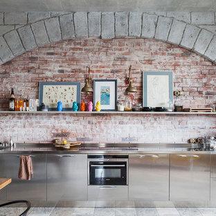 Imagen de cocina lineal, industrial, abierta, sin isla, con armarios con paneles lisos, puertas de armario en acero inoxidable, encimera de acero inoxidable, salpicadero marrón y electrodomésticos negros